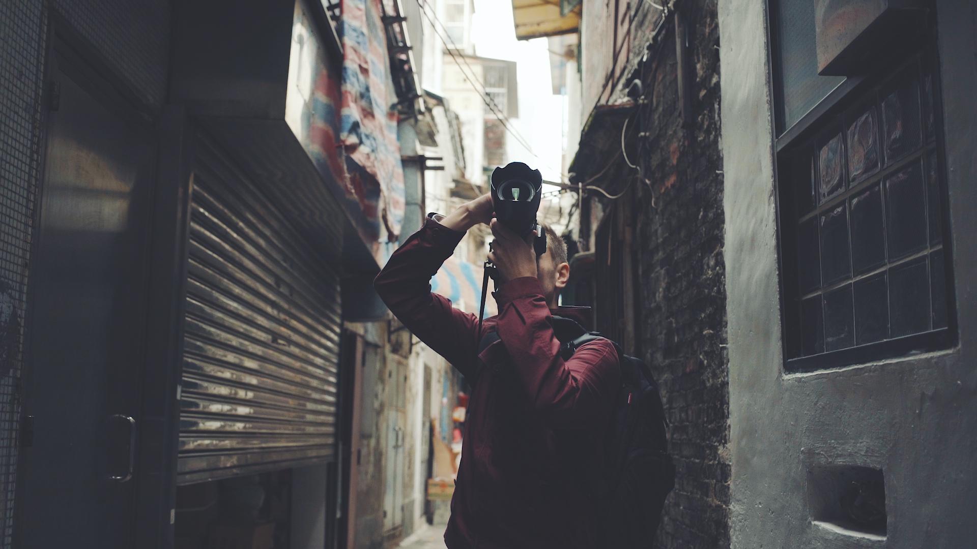 Joe taking photos in an alleyway in Macau